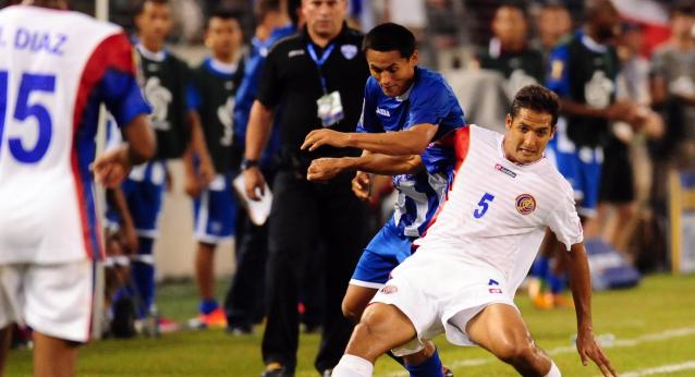 Jul 21, 2013; Baltimore, MD, USA; Costa Rica midfielder Celso Borges (5) fights for the ball with Honduras midfielder Andy Najar (14) at M&T Bank Stadium. Mandatory Credit: Evan Habeeb-USA TODAY Sports